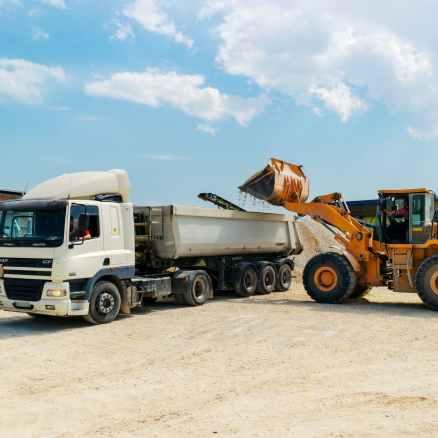 brown loader beside white cargo truck